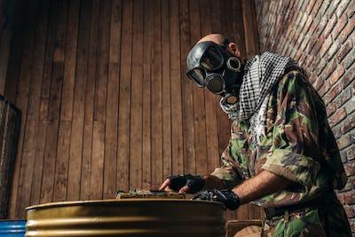 Terrorist in uniform sets bomb on the barrels