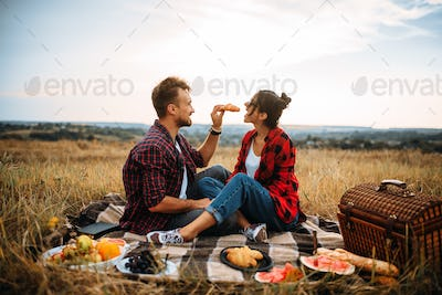 Happy love couple on picnic in summer field
