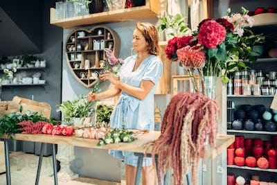 Floral artist sorts flowers on the table in shop