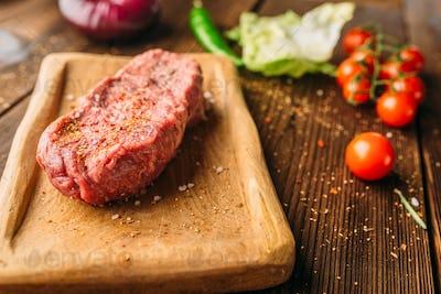 Juice piece of steak in seasoning and vegetables