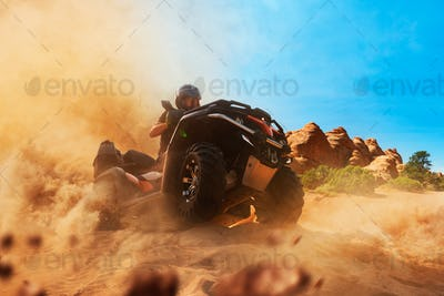 Quad bike rider climbing the sands, front view