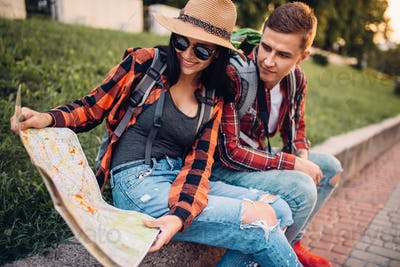 Couple of tourists study the map of attractions