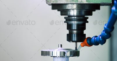 Precision industrial CNC machining of metal detail by mill at factory