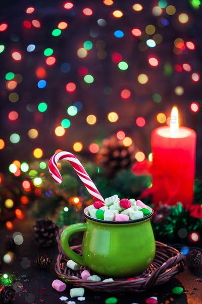 Green mug of hot chocolate with marshmallows and candy cane on h