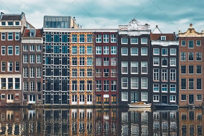 houses and boat on Amsterdam canal Damrak with reflection. Ams