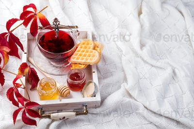 autumn fall concept with knitted blanket and hot tea with waffer, jam, honey on wooden tray on te