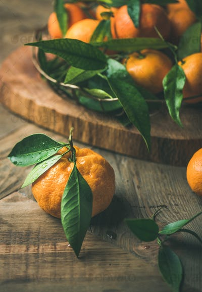 Fresh tangerines with leaves on board over wooden background