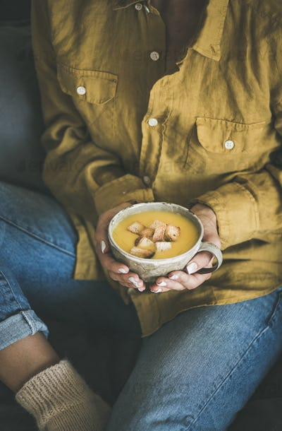 Woman sitting and holding warming pumpkin soup in mug