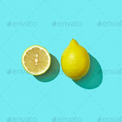 Fresh half and whole organic lemon on blue background with reflection of shadows and space for text