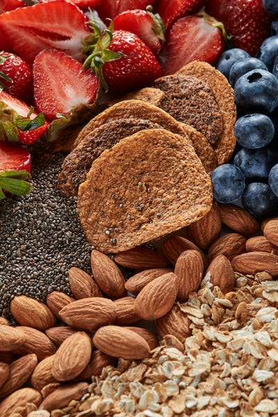 Uncooked healthy food ingredients - oat granola, strawberry, chia seeds, almond nuts, crunchies as a