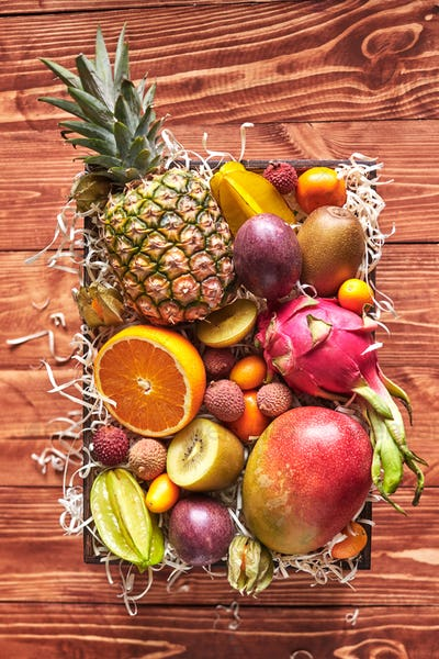 The box with exotic tropical fruits - fresh ripe pineapple, mango, dragon fruit, orange, carambola