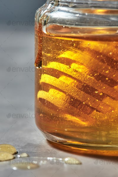 Close-up view of glass jar with golden honey and wooden dipper on a gray background. Jewish New Year