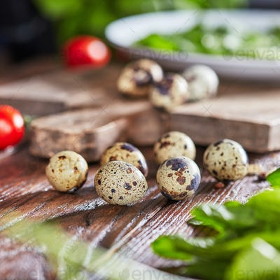 Healthy quail eggs on a wooden table with greens and tomatoes. Organic product