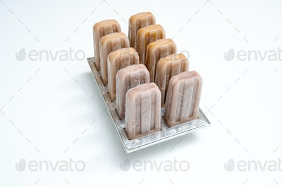 Plastic molds with coffee homemade ice cream on white background with copy space. Cold dessert