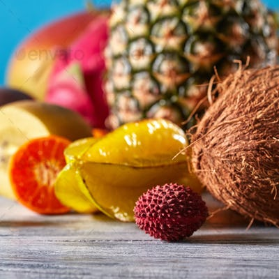 Close-up of tropical fruits - carambola, litchi, coconut, pineapple on a gray stone table