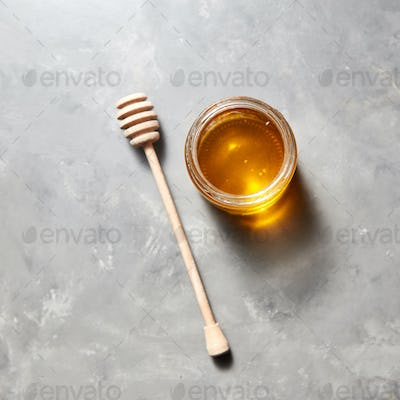Top view of glass jar with sweet meadow honey on a gray stone background. Jewish New Year healthy