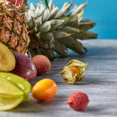 Close-up of exotic fruits on a gray wooden table - pineapple, carambola, kumquat, passion fruit