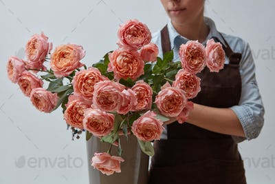 A girl in a brown apron holds a vase with pink roses on a gray background. Flower concept. Gift for