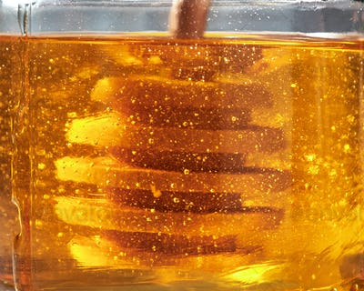 Macro close-up honey background with natural flower yellow dessert in glass pot with wooden dipper