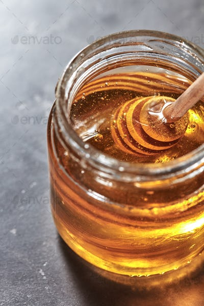 Wooden dipper in a glass jar with aromatic natural raw honey on a gray concrete table, pure organic