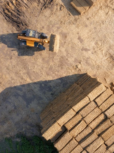 Aerial view from drone agricultural machine collecting bales of hay on a field. Farm industry. Top