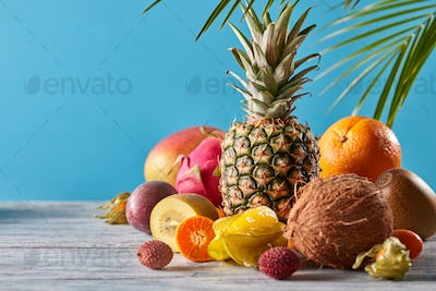 Creative exotic composition with tropical fruits and green leaves pineapple, coconut, mango, kiwi