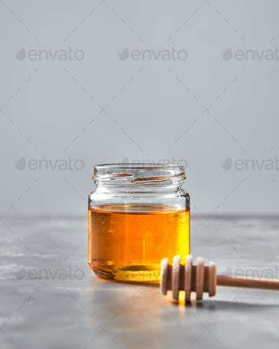 Sweet honey in a glass jar with wooden stick on a gray stone table. Jewish rosh hashanah holiday