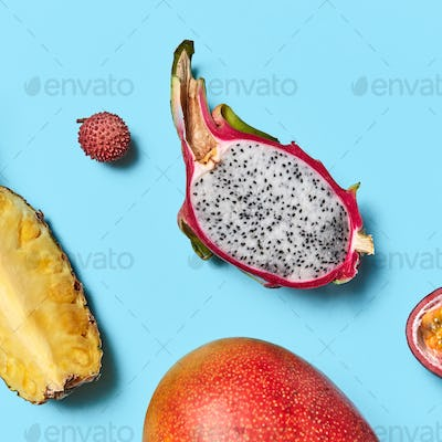 Closeup of juicy pineapple slices, pitahaya, passion fruit, and ripe mango on a blue background with
