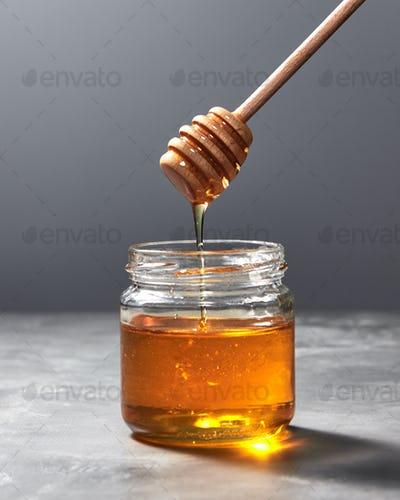 Fragrant organic fresh honey dripping from wooden stick to a glass pot on a gray marble table, pure
