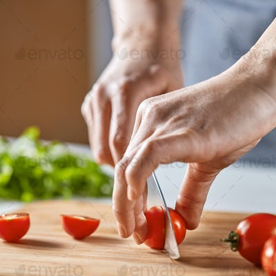 Hands girls cut red cherry tomatoes on a wooden board. Step by Step Cooking Healthy Salad