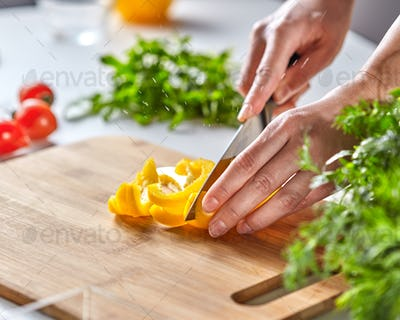 Organic ripe peppers cut the hands of a woman on a wooden board. On the kitchen table, tomatoes and