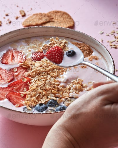 Female hand takes the spoon with organic yogurt smoothie , strawberries, blueberry, oat flakes, nuts