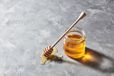 Fragrant organic fresh honey dripping from wooden stick to a glass pot on a gray concrete table