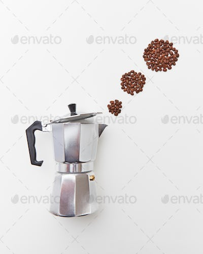 Metal Italian coffee maker with coffee beans in the form of a circles of steam on a white background