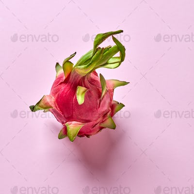 View from above to tropical fruit - pitahaya with green leaf on a pink background, copy space. Top