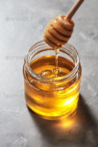 Natural sweet golden dripping honey in a glass pot with dipper on a gray stone table. Rosh hashanah