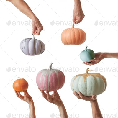 Freshly painted handmade colorful pumpkin in a pastel colors holding by hands on a white background