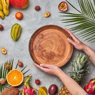 Hands of a woman holding a brown empty plate around a different tropical fruit ripe on a gray