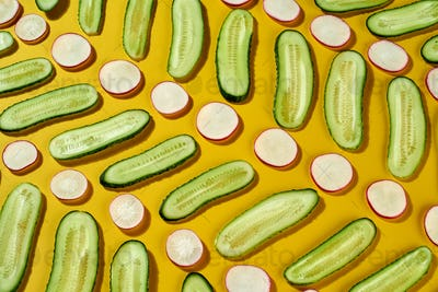 Organic healthy spring vegetables - slices of cucumber, radish in a creative diagonal pattern on a