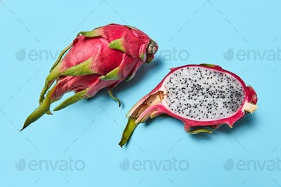 A dragon fruit, or pitahaya represented on a blue background with a copy space. Ripe tropical fruit