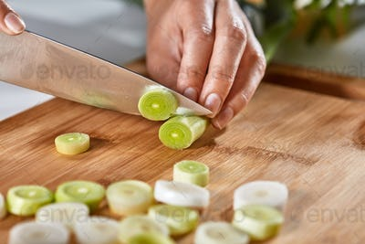 The girl's hands cut organic leek into pieces on a wooden board. Healthy food