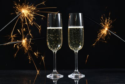 glasses with champagne and sparkles