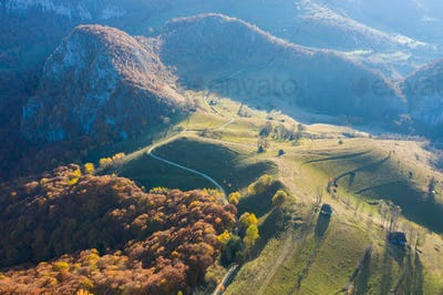Aerial drone scene of autumn countryside landscape with wooden houses, thatched roof and dirt road