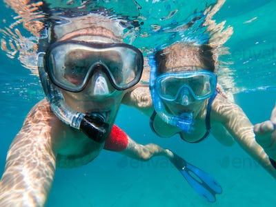 Snorkeling couple in love taking selfie underwater