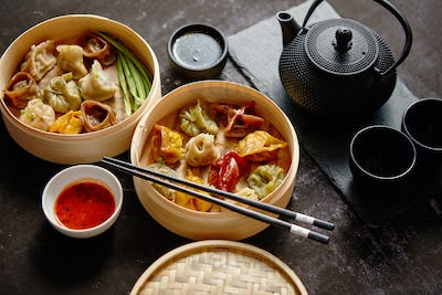 Composition of chinese food. Mixed kinds of dumplings from wooden bamboo steamer