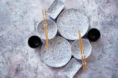 Empty oriental style dishware set on gray stone background