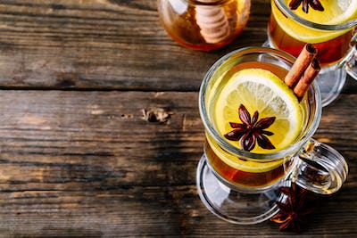 Hot spiced Apple cider Toddy with lemon, honey and cinnamon stick in glass on wooden background