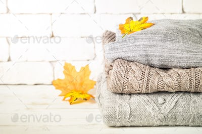 Stack of cozy woolen clothes on white