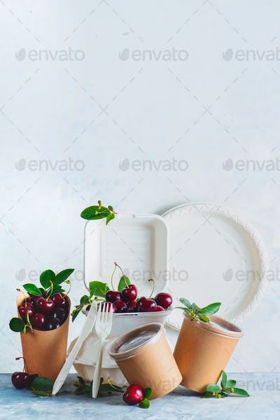 Catering disposables, cups, plates and containers with cherries. Eco-friendly food packaging on a