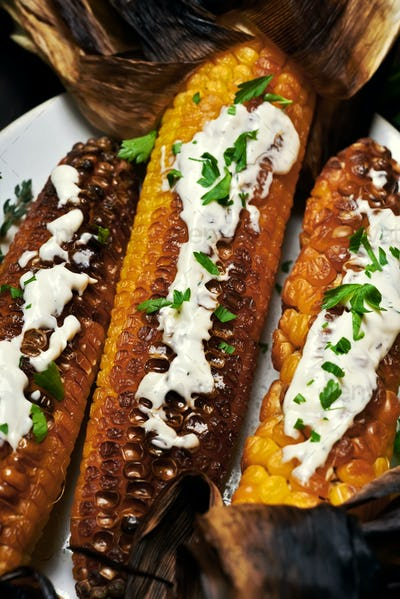Grilled corn cobs on plate, top view